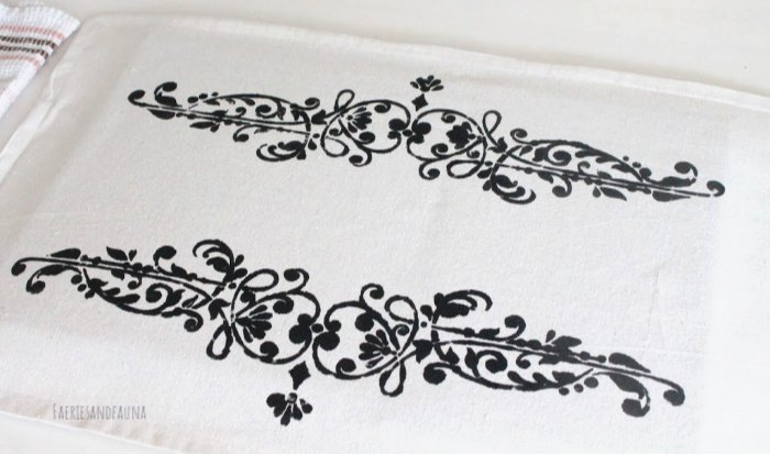 The stencilled front of a DIY cushion cover made with drop cloth.