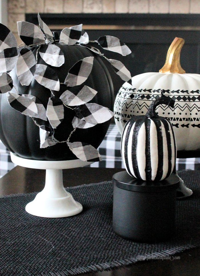 Fall vignette featuring a DIY pumpkin craft that has buffalo check leaves and a black and white pumpkin.