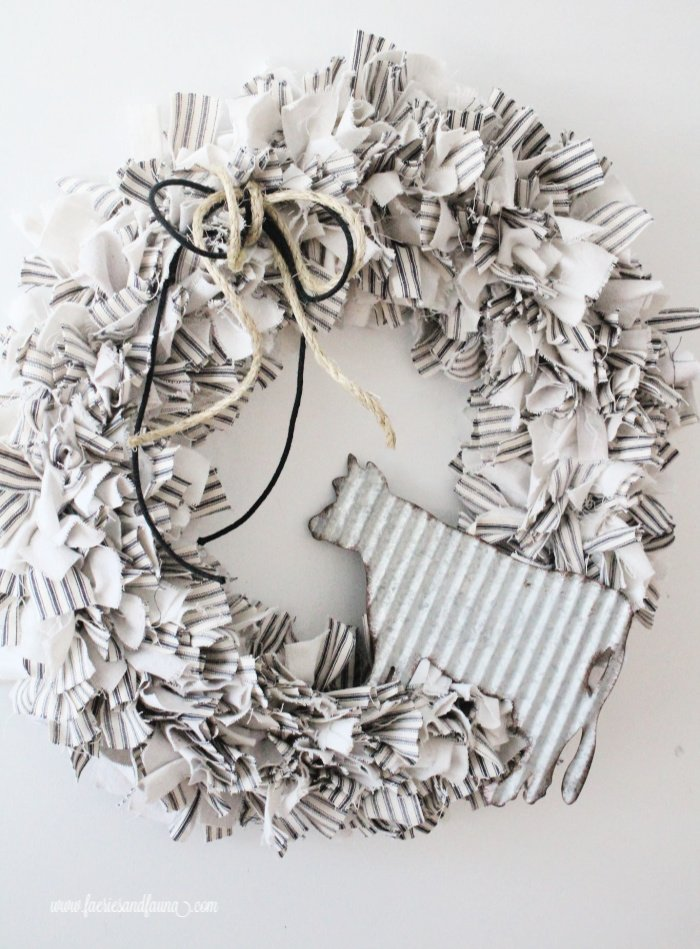 A DIY farmhouse rag wreath decorated with twine and galvanized cow