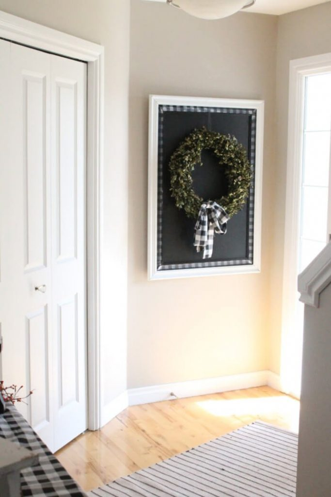 A front entry decorated with a large DIY chalkboard as a backdrop to a pretty wreath.