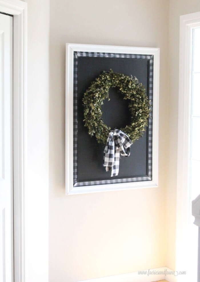 a large diy chalkboard with buffalo check trim, with a simple wreath.