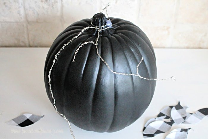 Building a wire frame for DIY fabric leaves made with buffalo check on a Fall pumpkin craft.
