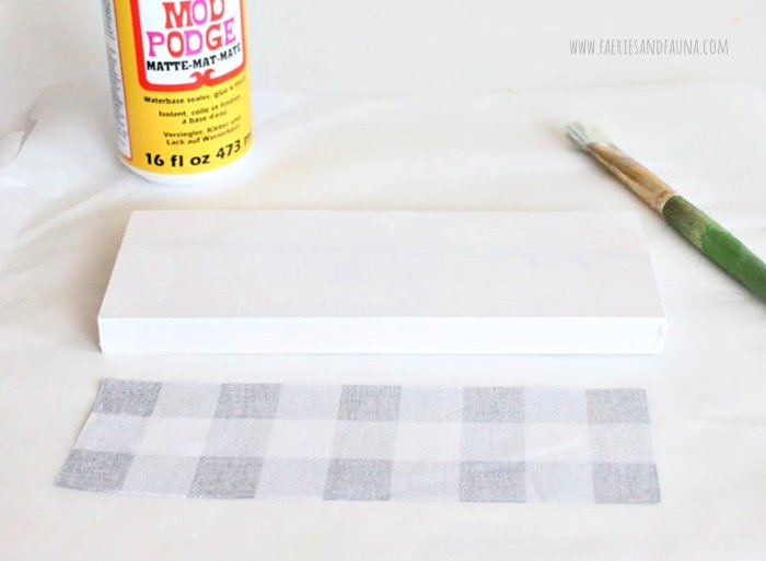 Use mod podge to glue buffalo check fabric to a DIY wood sign for Fall.