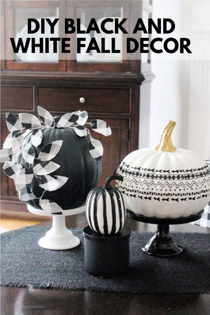 A dramatic black Fall pumpkin vignette with DIY wire leaves on a black chalkboard pumpkin. There are three different black and white pumpkins all sitting on pedestals in for neutral Fall livingroom decor.
