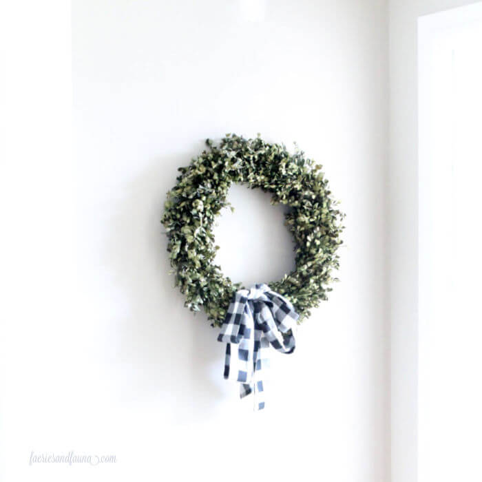 A wreath hanging on the wall before it has a backdrop