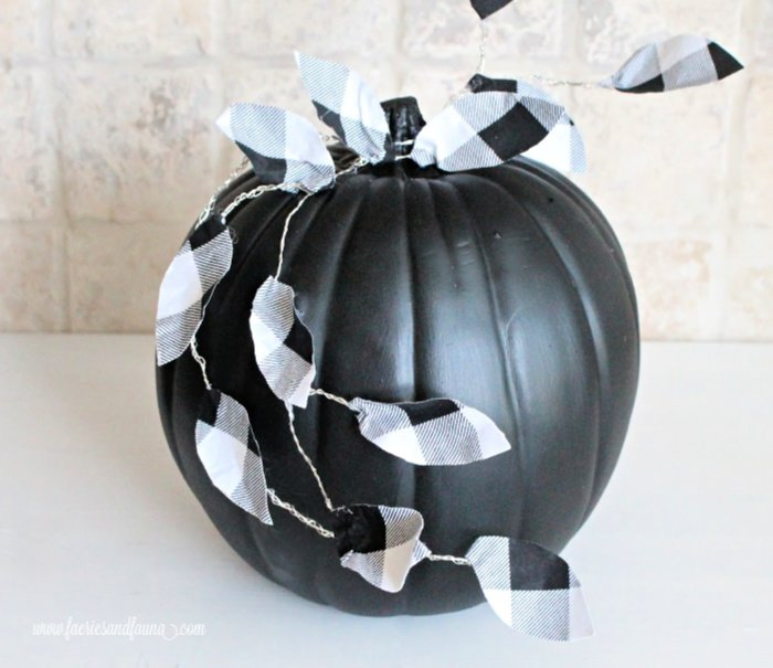 Attaching leaves to a DIY Fall pumpkin craft.