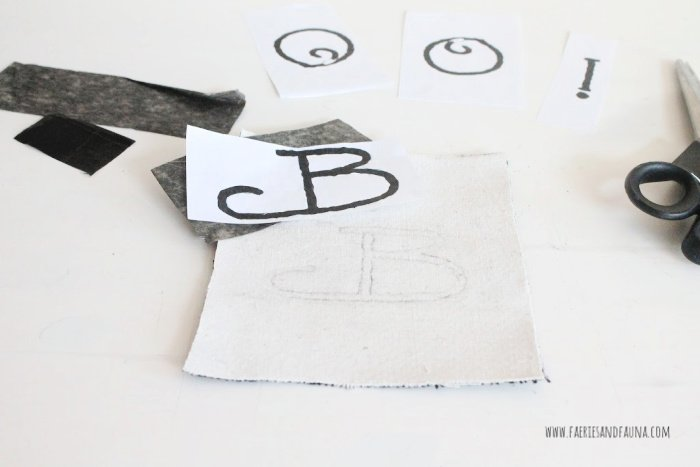 Transferring lettering onto fabric using carbon paper.