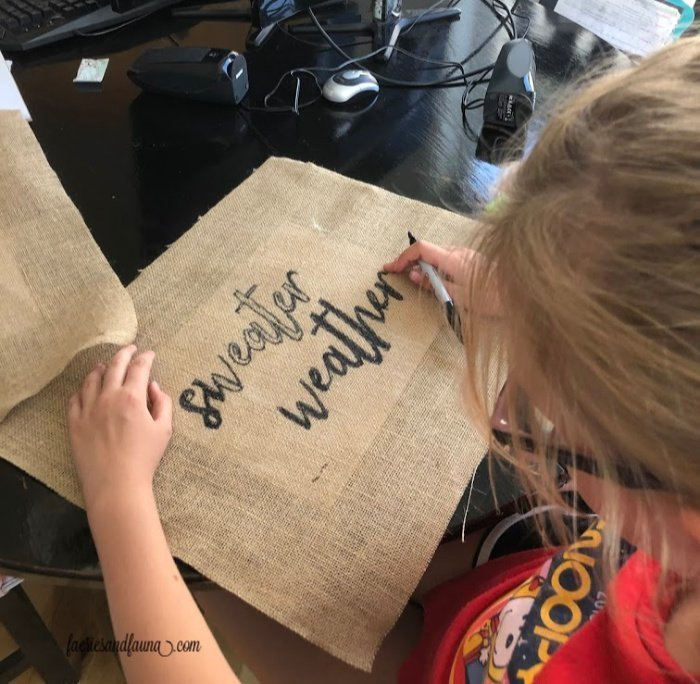 Baby girl colouring in the outline of a burlap sign for Fall