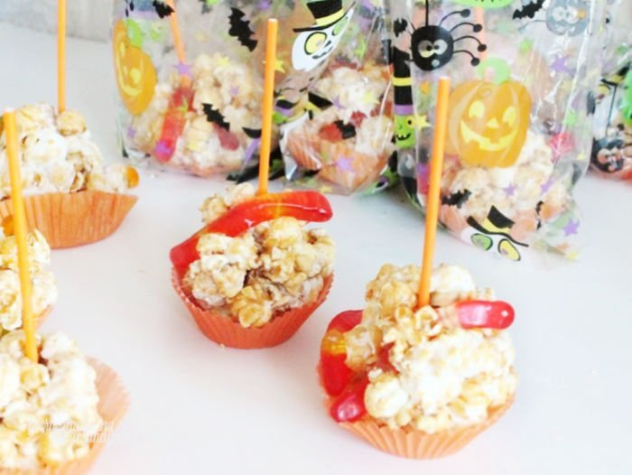 Adding sticks to popcorn balls for Halloween treats for a kids Halloween party