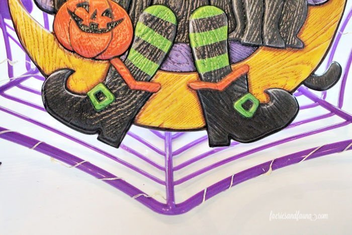How to glue a flat ornament to a basket to make a dollar store DIY Halloween wreath.