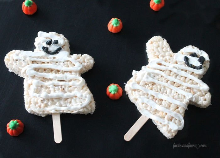 Close up of two ghost mummy Halloween treats on sticks for a kid's Halloween school party.