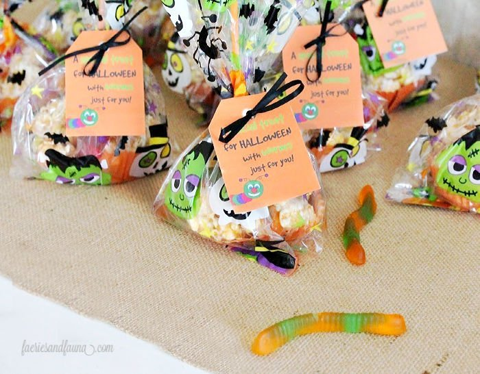 Halloween treat packages with popcorn, marshmallow,caramel and gummy worms with a fun label.