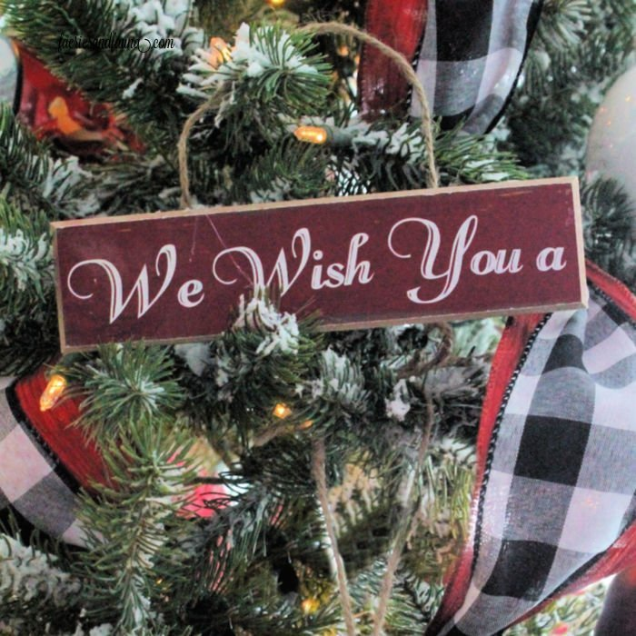 A handmade Christmas ornament hanging on the Christmas tree made of wood with letters.
