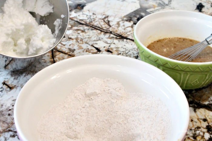 Egg whites, flour and molasses ingredients for a gingerbread waffle recipe.