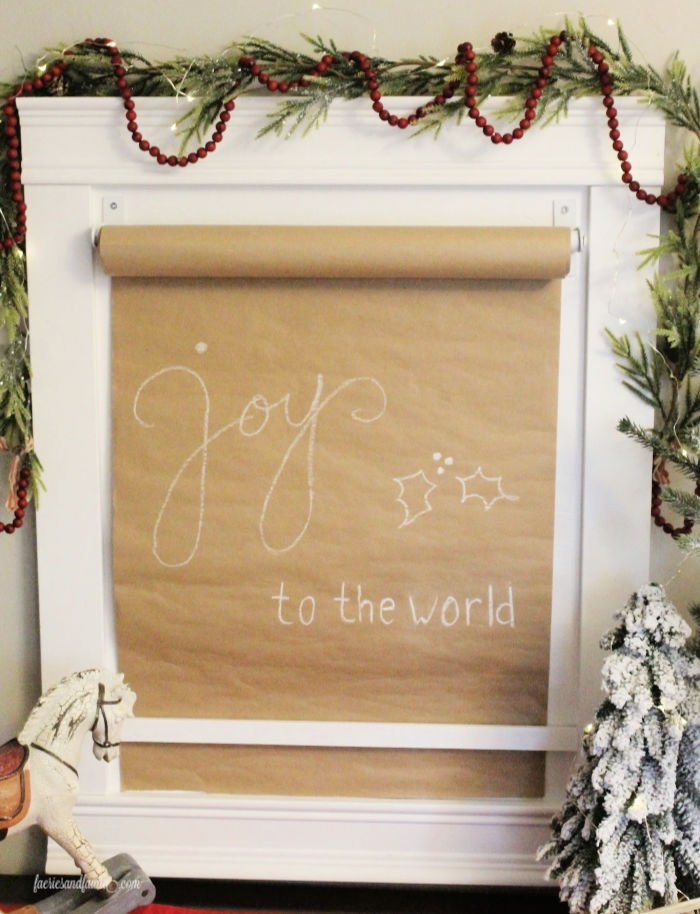 A DIY paper scroll sign with Christmas lettering and a DIY paper roll holder.