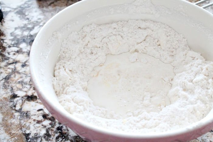 Making a well in flour for making homemade Cranberry Scone recipe.