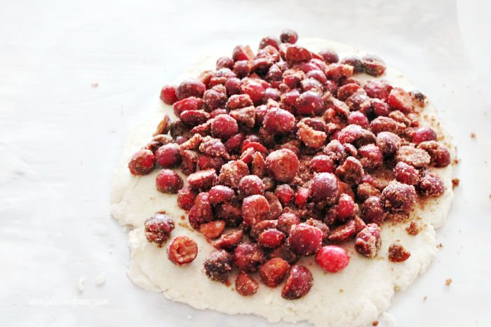 Cinnamon and sugar coated cranberries piled on top of scone dough while make a cranberry scone recipe.
