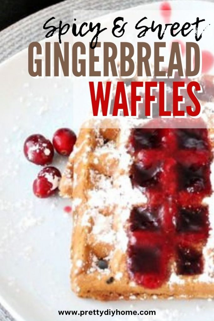 Spicy golden gingerbread waffles with cranberry syrup and icing sugar topping.
