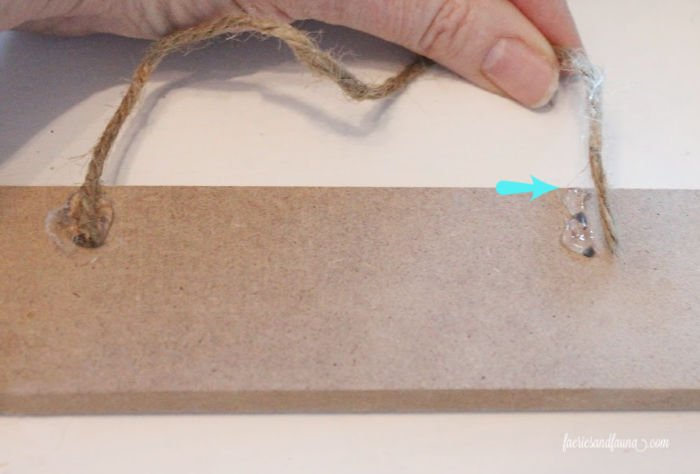 Gluing twine onto wood for DIY Christmas Store ornaments using dollar store supplies
