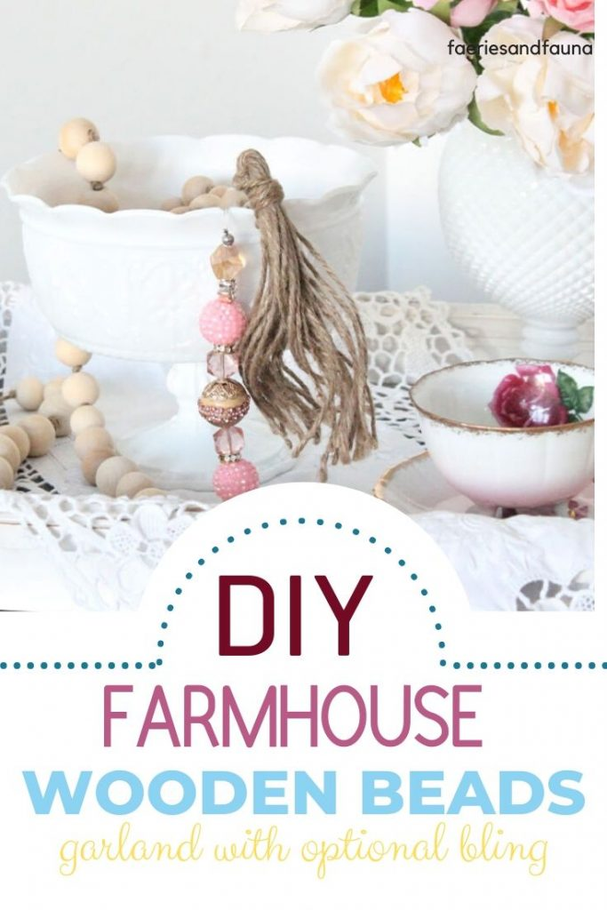 DIY natural wooden farmhouse beads with pink bling beads on the end for Valentine's day. The beads are part of a Valentine centerpiece with white milk glass vase and lace tablecloth.