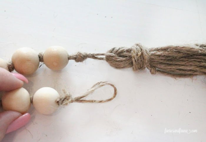 Closing the end loop of a diy farmhouse bead garland with tassels.