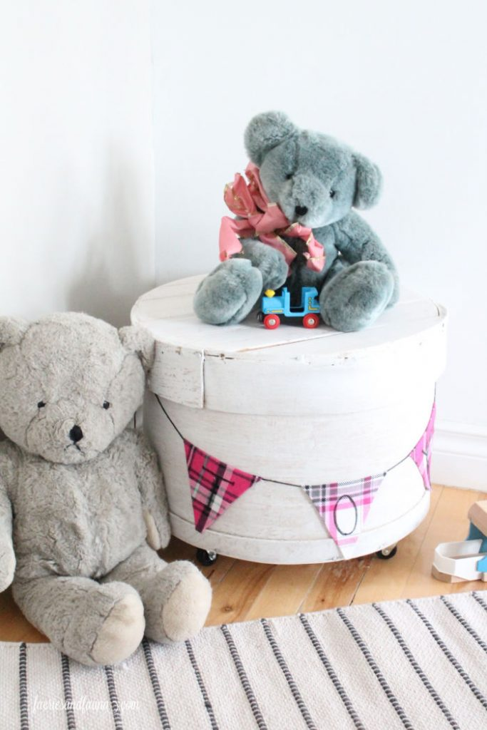 A vintage round wooden cheese box repurposed into a farmhouse storage bin. A really pretty farmhouse upcycle project. for toys.