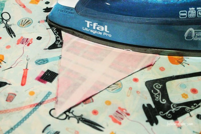 Ironing fabric to create hems on a DIY fabric pennant for a toy box.