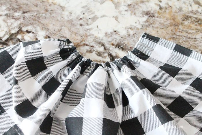 Gathering buffalo check fabric for making an apron to attach to a DIY Easter bunny craft.