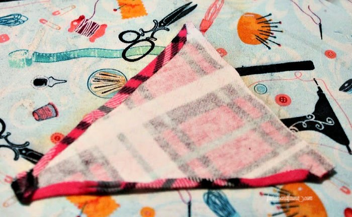 Folding over the edges of a fabric pennant for toys.