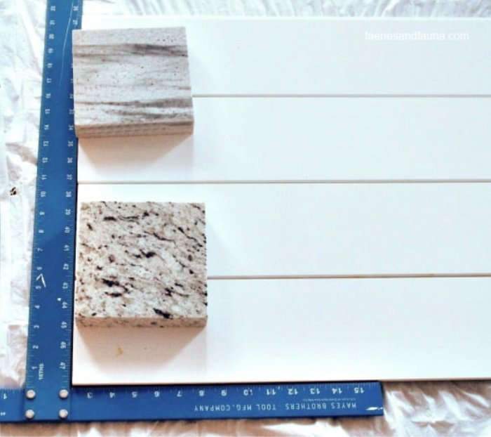 Using a square to line up shiplap for a farmhouse backdrop for decorating.