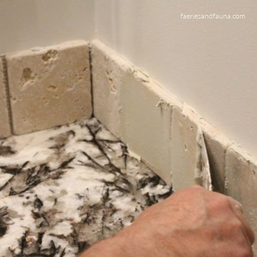 Filling in the spaces between tiles with grout.
