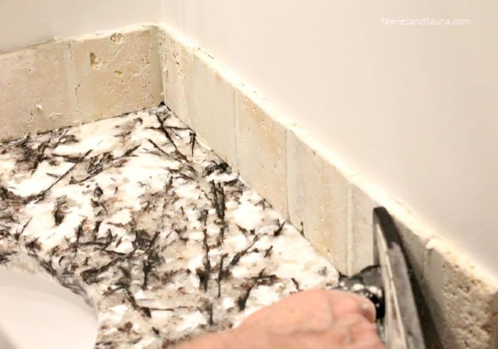 Using a rubber trowel to smooth out grout on a DIY tile back splash