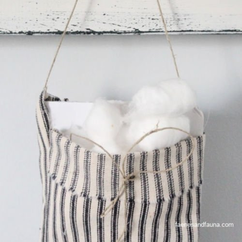 Adding cotton balls and essential oils to a DIY fabric pouch.
