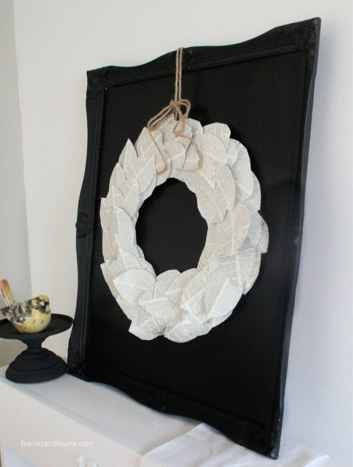 A DIY farmhouse wreath made using book pages mounted onto a DIY black chalkboard.