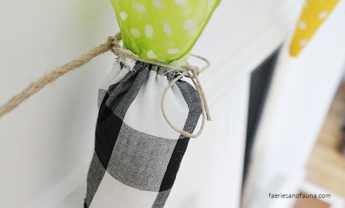 Tying DIY fabric carrots to twine to make a Easter Banner