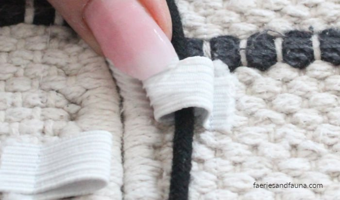 Lacing cord through elastic to create a DIY large dog mat.