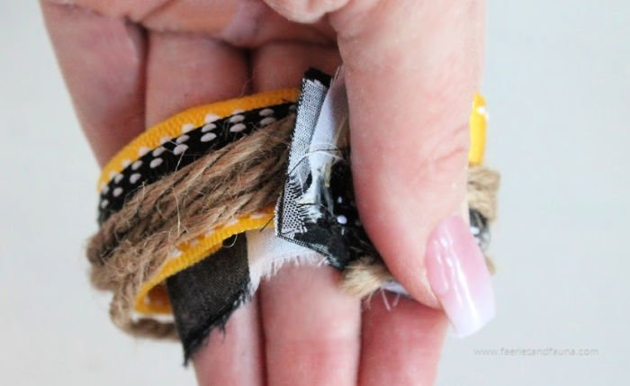 Making a messy bow by holding ribbon in one hand.