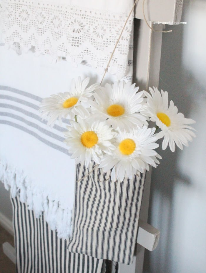 A small farmhouse pouch with flowers hanging on a ladder for farmhouse decor.