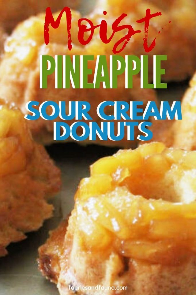 A dozen homemade Pineapple glazed sour cream baked donuts. They are golden and baked in a baking pan, with little tidbits of pineapple and a brown sugar glaze.