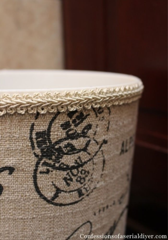 DIY monogrammed waste basket hack in cream and place with a pretty corded top.