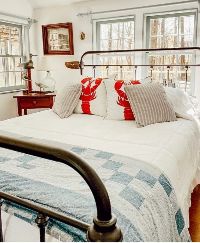 Gorgeous coastal designed bedroom with iron bed, lobster pillows and a homemade quilt.