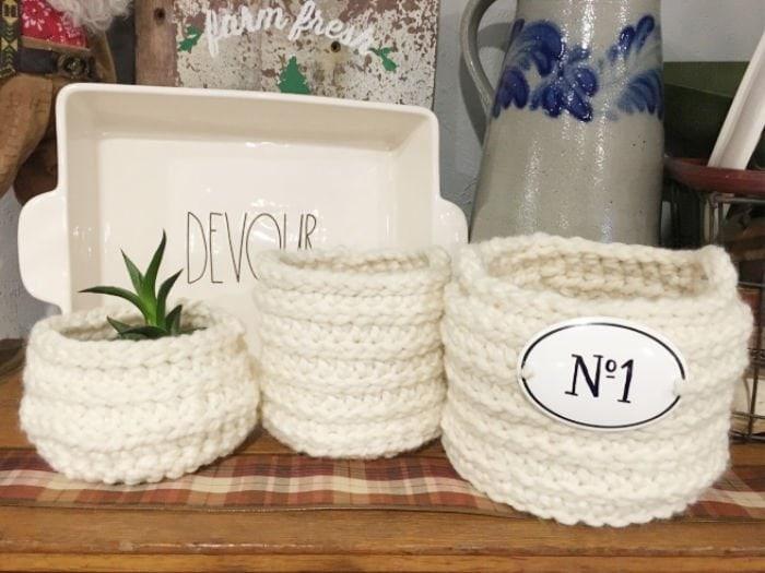 Three chunky homemade crochet baskets on a shelf in farmhouse style.