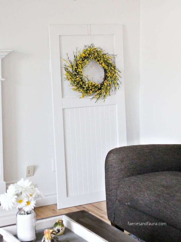 A handmade farmhouse door for farmhouse decor. Its white with tongue and groove and has a pretty yellow wreath.