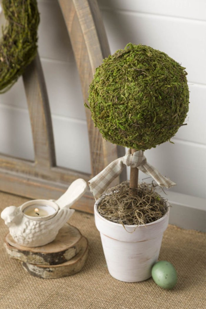 A homemade topiary with moss and a pretty bird candle.