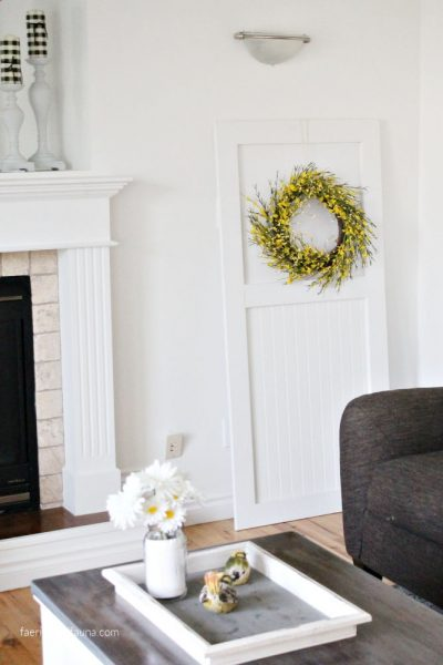 A DIY farmhouse door in white with shiplap for interior farmhouse decor. A pretty white backdrop with tongue and groove and a pretty wreath.
