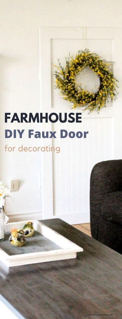 A small handmade DIY faux door for decorating. The door is wooden, painted white and has a yellow wreath hanging on it. It sits in the corner of the livingroom and their is a small white tray on a table in front of it.