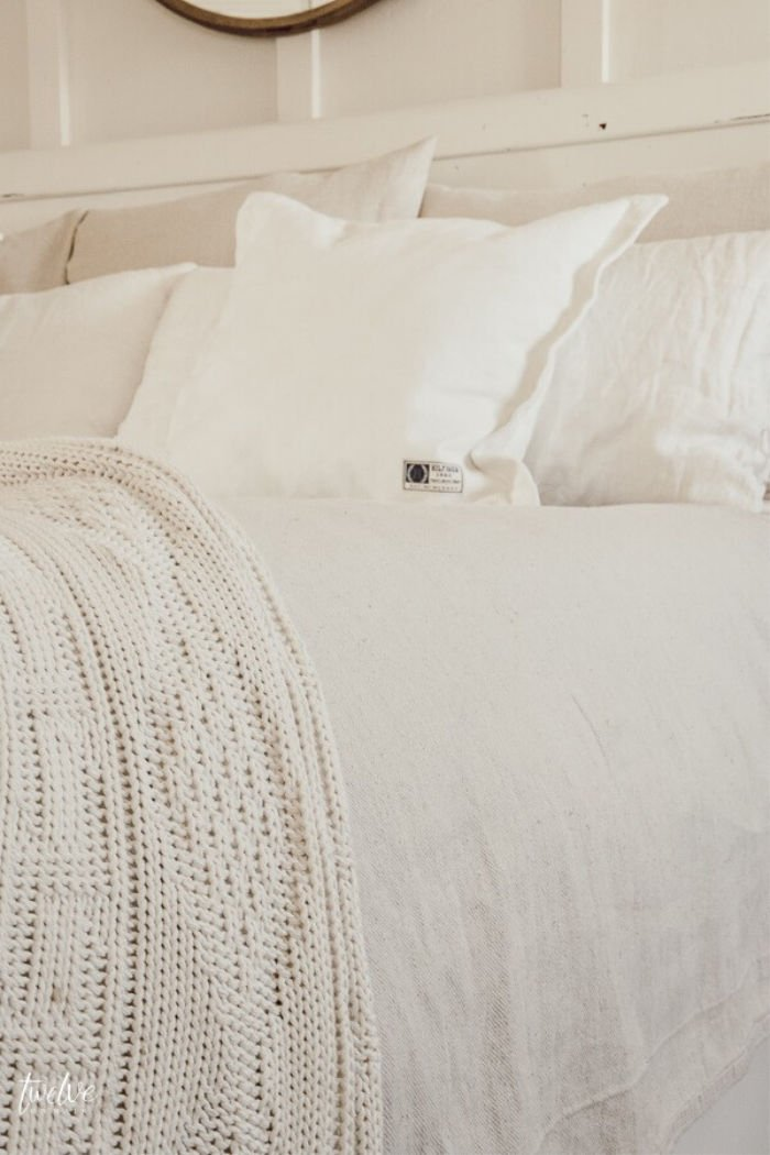 DIY drop cloth bedding hack, on the bed with white cushions and cream coloured farmhouse throw. A pretty farmhouse bed.