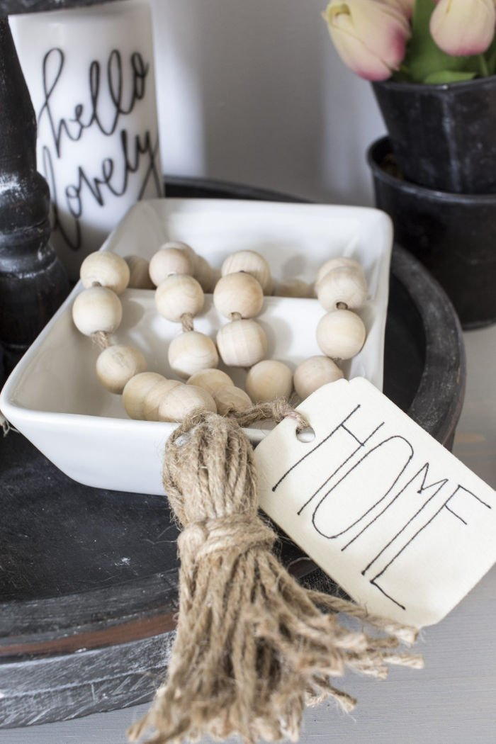 A farmhouse natural wood bead garland with tassles and a label that says home. Showing in a pretty farmhouse display on a grey tray.