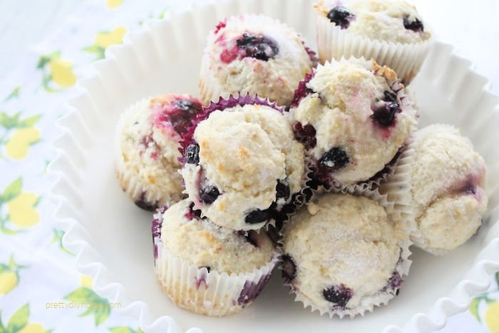 A bowl full of pretty blueberry lemon muffins in a white bowl. They have a light dusting of white sugar on top.