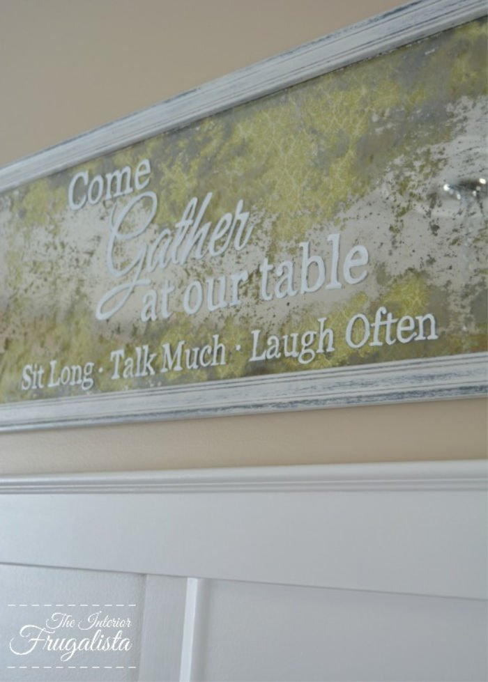 A faux antiqued mirror sign that says Come Gather at our table.